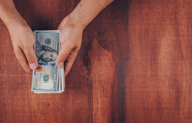 Draufsichtmann, der hundert dollarnoten auf holz hält Kostenlose Fotos