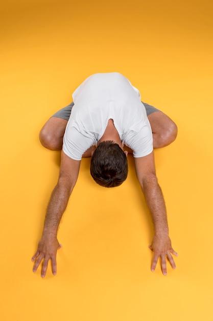 Draufsichtmann, der in yogahaltung ausdehnt Kostenlose Fotos