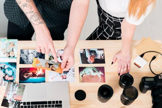 Draufsichtmann und -frau, die mit fotos und laptop arbeiten Kostenlose Fotos