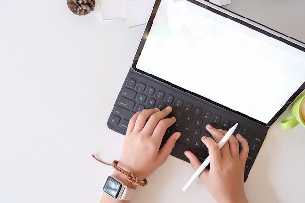 Draufsichtmannhand, die intelligente tastaturtablette auf weißer tabelle am studioarbeitsplatz schreibt Premium Fotos
