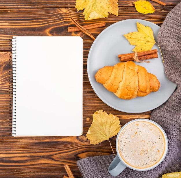 Draufsichtnotizbuch umgeben durch kaffee und hörnchen Kostenlose Fotos