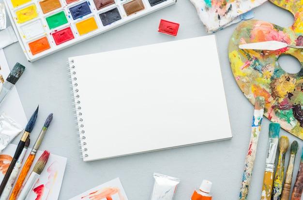 Draufsichtnotizbuch umgeben durch malende elemente Kostenlose Fotos