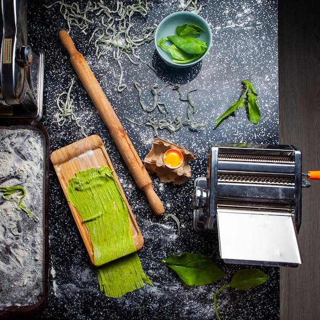 Draufsichtnudeln und küchenwerkzeuge einschließlich walze mit blättern in einer schüssel auf schwarzem strukturiertem hintergrund. Kostenlose Fotos