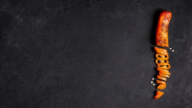 Draufsichtpeperoni auf schwarzem hintergrund mit kopienraum Premium Fotos