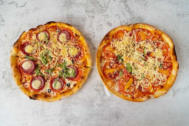 Draufsichtpizzas auf zementhintergrund Kostenlose Fotos