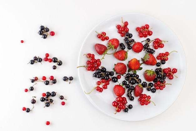 Draufsichtplatte mit erdbeeren frisch und mild mit bluberries und preiselbeeren auf der weißen hintergrundfarbe frische milde fruchtbeere Kostenlose Fotos