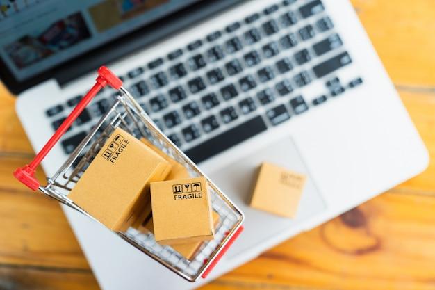 Draufsichtproduktpaketkästen im warenkorb mit laptop-computer für das on-line-einkaufs- und lieferungskonzept Premium Fotos