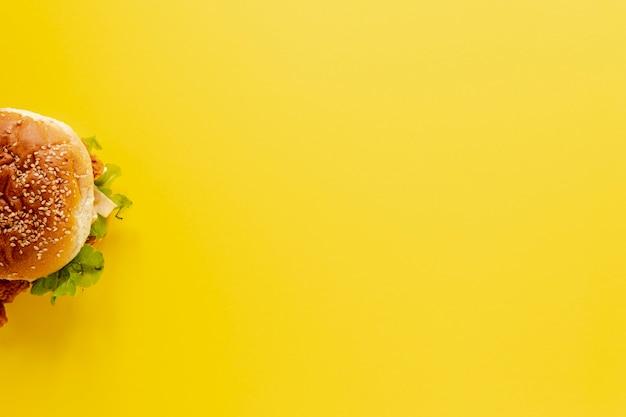 Draufsichtrahmen mit halbem burger und gelbem hintergrund Kostenlose Fotos