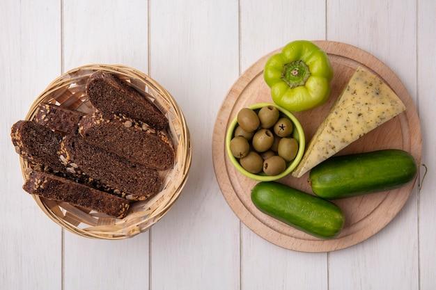 Draufsichtscheiben von schwarzbrot mit käse und gurken mit paprika auf einem ständer mit oliven auf einem weißen hintergrund Kostenlose Fotos