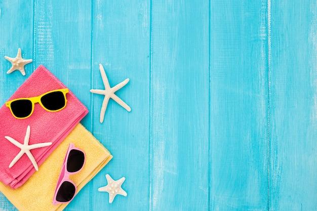 Draufsichtstrandkonzept mit tuch, gläsern und starfish auf blauem hölzernem hintergrund Kostenlose Fotos