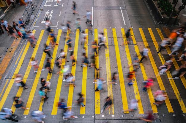 Draufsichtszene von bewegung unscharfen nicht erkennbaren fußgängern der menge, die über der hong kong-straße um mongkok-station kreuzen, gelbes farbzebra ist das zeichen von hong kong-transport und -zebrastreifen Premium Fotos