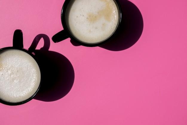 Draufsichttassen kaffee auf rosa hintergrund Kostenlose Fotos