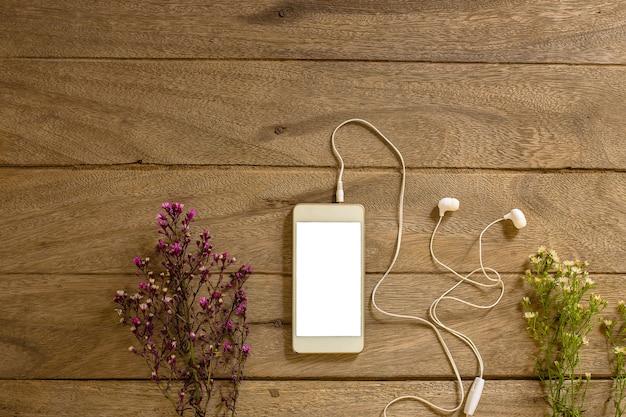 Draufsichttelefon und kopfhörerholzhintergrund Premium Fotos