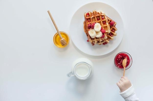 Draufsichtwaffel mit marmelade, milch und honig Kostenlose Fotos