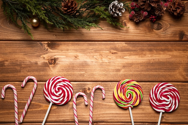 Draufsichtweihnachtsbonbons mit hölzernem hintergrund Kostenlose Fotos
