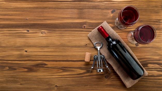 Draufsichtweinflasche mit glas auf hölzernem hintergrund Kostenlose Fotos