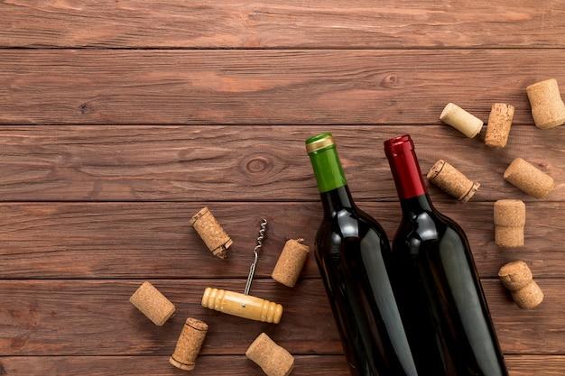 Draufsichtweinflaschen auf hölzernem hintergrund Premium Fotos