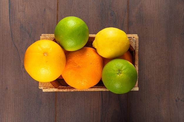 Draufsichtzitrusfrüchte in der holzkiste auf holztisch Kostenlose Fotos