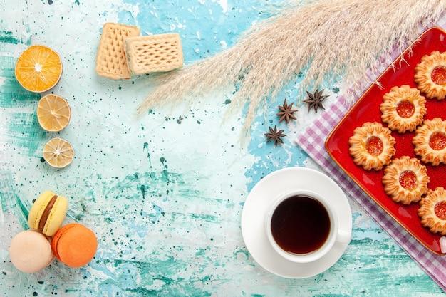 Draufsichtzuckerplätzchen innerhalb der roten platte mit tasse tee und macarons auf hellblauem hintergrund Kostenlose Fotos