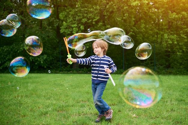 Draußen porträt des niedlichen vorschuljungen, der seifenblasen bläst Premium Fotos