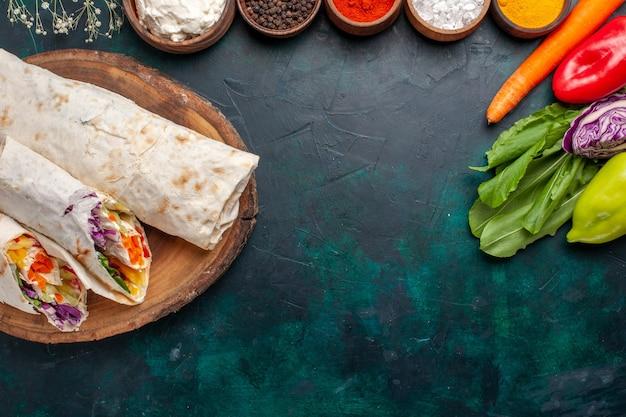 Draußenansicht köstliches fleischsandwich aus fleisch am spieß mit gewürzen und gemüse auf blauem schreibtisch gegrillt Kostenlose Fotos