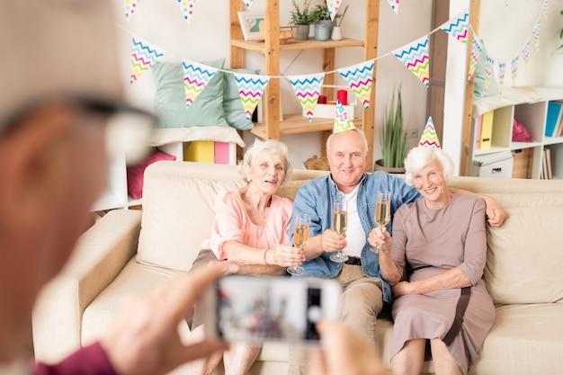 Drei ältere freunde mit champagnerflöten sitzen auf der couch beim anstoßen zum geburtstag Premium Fotos