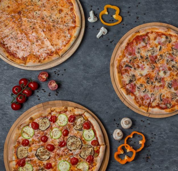 Drei arten pizza mit mischbestandteilen Kostenlose Fotos