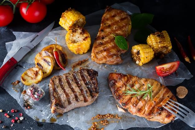 Drei arten von gegrilltem fleisch mit gemüse und gewürzen auf papier Premium Fotos
