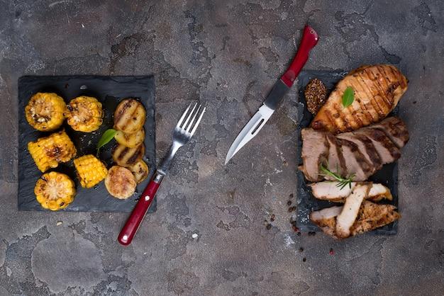 Drei arten von gegrilltem steak (huhn, schweinefleisch, rindfleisch) auf schieferplatte mit kräutern Premium Fotos