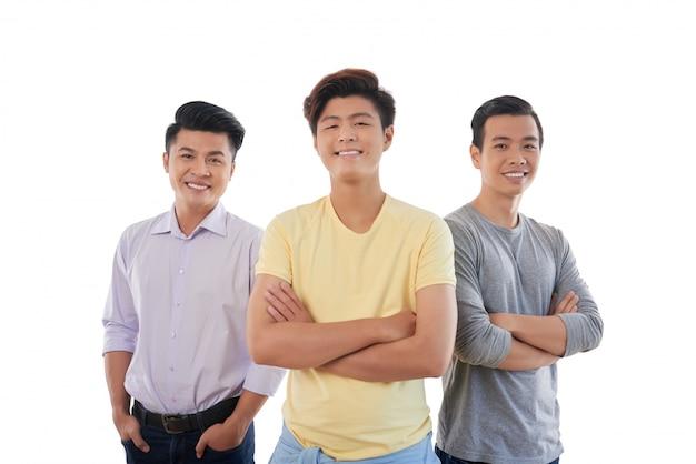 Drei asiatische männliche stehende und lächelnde freunde Kostenlose Fotos