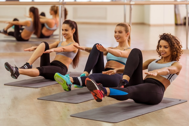 Drei attraktive lächelnde sportmädchen beim handeln von abs. Premium Fotos