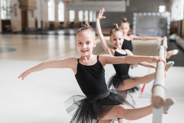 Drei ballerinamädchen im schwarzen ballettröckchen, das ihre beine auf stange ausdehnt Kostenlose Fotos