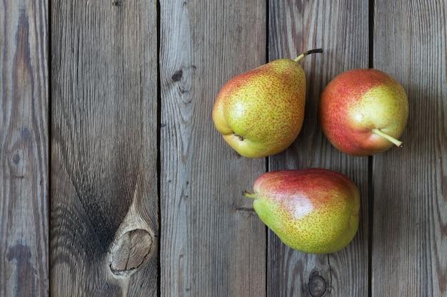 Drei birnen auf einem naturholztisch. speicherplatz kopieren Premium Fotos