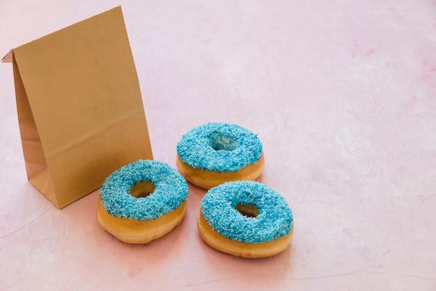 Drei blaue donuts mit paket auf rosa hintergrund Kostenlose Fotos