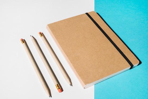 Drei bleistifte und geschlossenes notizbuch mit brauner abdeckung Kostenlose Fotos