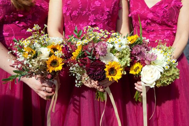 Drei brautjungfern in lila spitzenkleidern mit frischen blumensträußen Premium Fotos