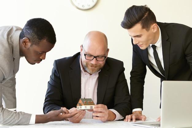 Drei büromänner schätzen das modell eines zukünftigen reihenhauses. kaukasischer ingenieur in gläsern, die miniatur halten und lächeln. andere kollegen in anzügen schauen sich mit interesse ein winziges haus an. Kostenlose Fotos