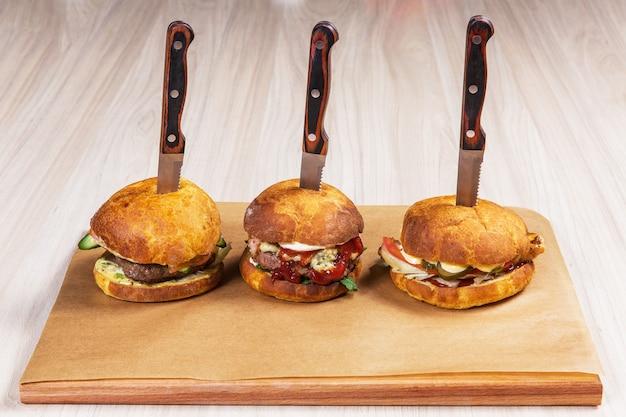 Drei burger mit messern auf hellem holztisch in einem restaurant. fast food Premium Fotos