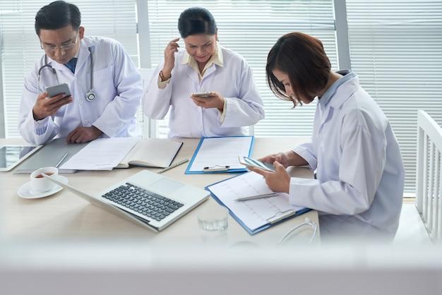 Drei doktoren beschäftigt, ihre geräte verwendend Kostenlose Fotos
