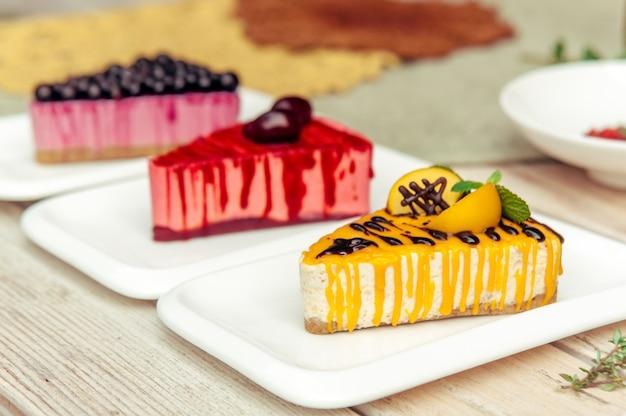 Drei dreieckige kuchenstücke mit aprikosenpflaume und johannisbeere auf rustikalem holztisch Premium Fotos