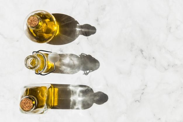 Drei flaschen reines gesundes olivenöl mit schatten auf boden Kostenlose Fotos