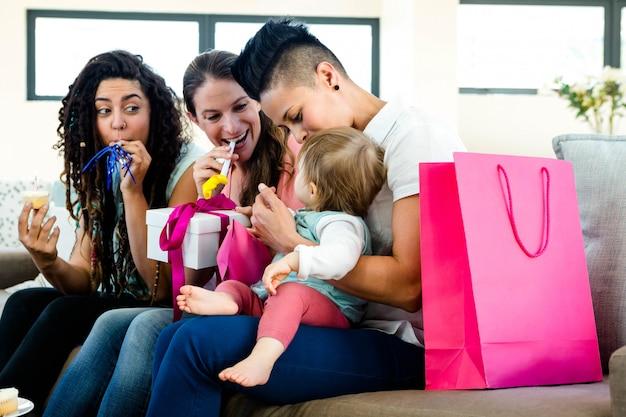 Drei frauen, die auf einer couch feiert ersten geburtstag eines babys sitzen Premium Fotos