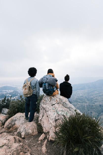 Drei freunde auf der gebirgsspitze, die ansicht betrachtet Kostenlose Fotos