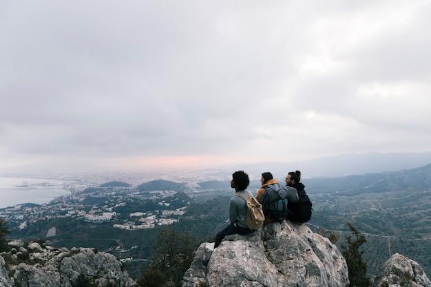 Drei freunde, die auf die oberseite des berges sitzen, die szenische ansicht genießend Kostenlose Fotos