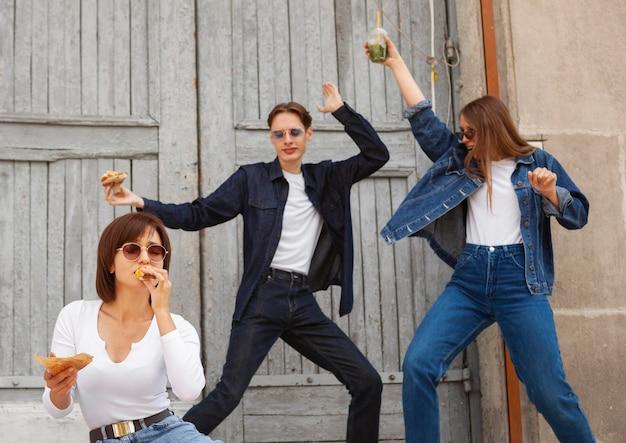 Drei freunde, die spaß draußen beim essen des burgers haben Kostenlose Fotos