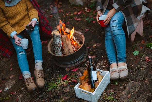 Drei freunde entspannen sich gemütlich und trinken abends im freien wein am feuer im hinterhof. Premium Fotos