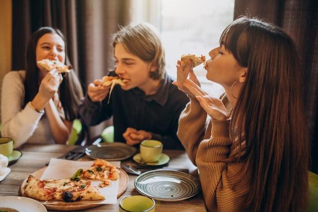 Drei freunde essen zusammen pizza in einem café Kostenlose Fotos