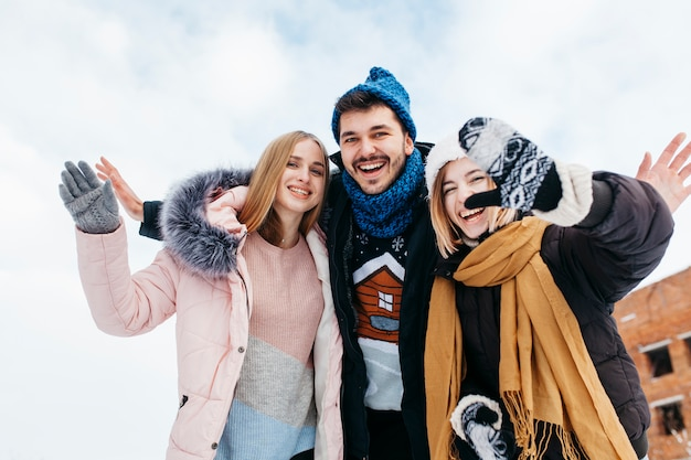 Drei freunde in der winterkleidung, die draußen mit den händen wellenartig bewegt Kostenlose Fotos