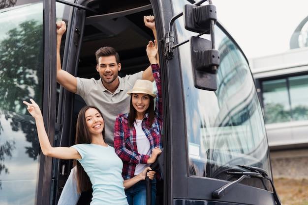 Drei freunde von touristen gucken aus den bustüren Premium Fotos