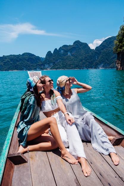 Drei freundinnen von touristen reisen um khao sok nationalpark, im urlaub in thailand. segeln auf asiatischem boot auf see am sonnigen tag, mit herrlicher aussicht. Kostenlose Fotos